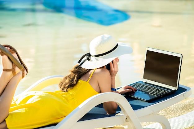 Jovem mulher vestida de amarelo está deitada na cadeira de praia, trabalhando no computador em um resort de verão.