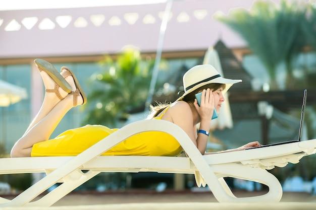 Jovem mulher vestida de amarelo está deitada na cadeira de praia, trabalhando no computador portátil, tendo uma conversa no celular no resort de verão. fazendo estudos durante a viagem conceito.