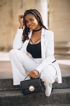 Jovem mulher vestida de branco, sentado na escada