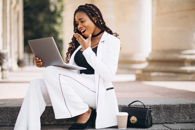 Jovem mulher vestida de branco usando laptop