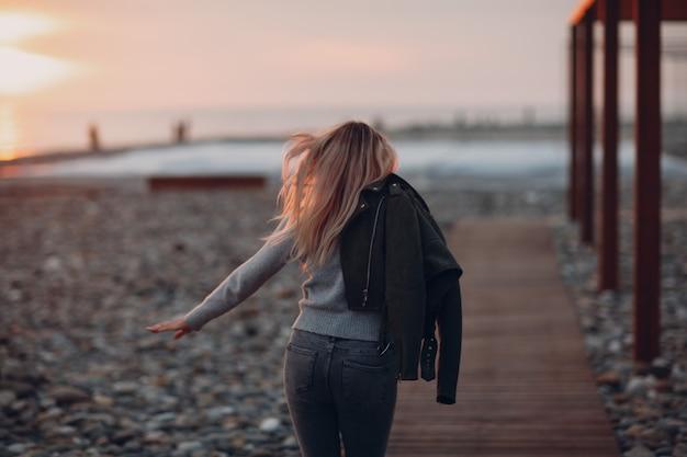 Jovem mulher vestida de jeans e blusa na praia de seixos à beira-mar.