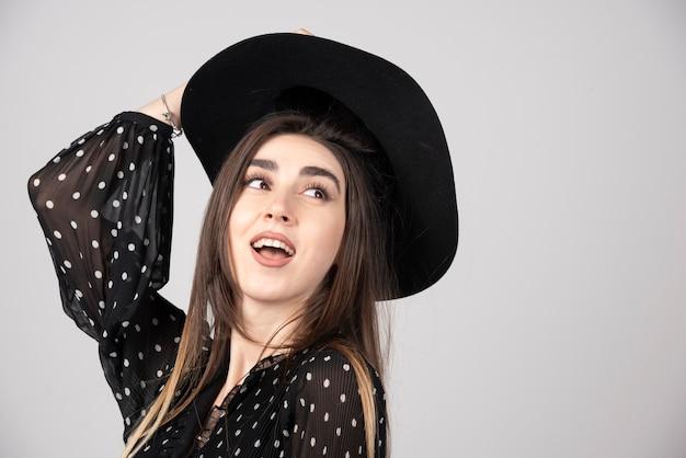 Jovem mulher vestida de preto, segurando o chapéu no topo da cabeça.