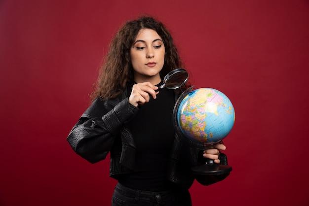 Jovem mulher vestida de preto, segurando um globo com lupa.