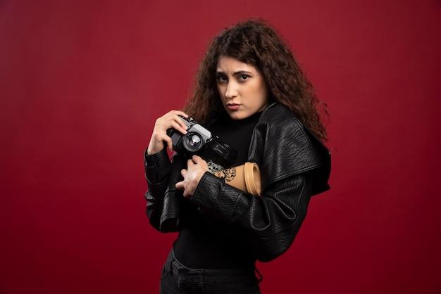 Jovem mulher vestida de preto, segurando uma xícara e uma câmera.