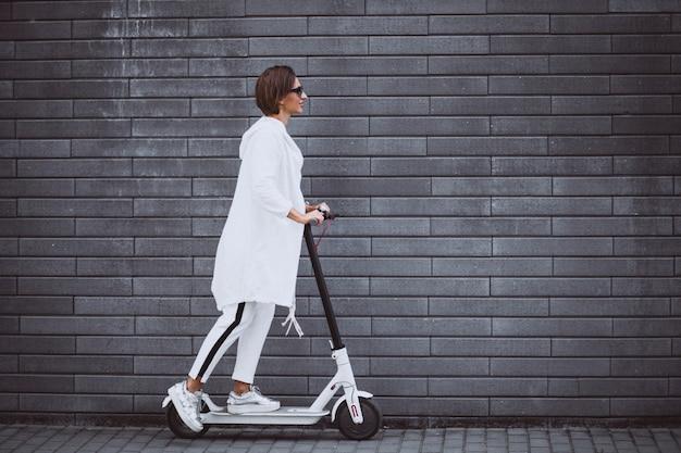 Jovem mulher vestida de scooter de equitação branca