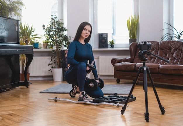 Jovem mulher vestida de sportswear azul escuro prepara seu equipamento na sala de estúdio com fotocâmera.