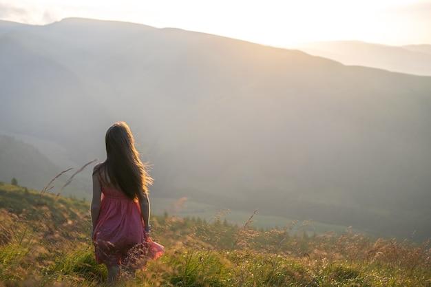 Jovem mulher vestida de vermelho andando no campo de grama em uma noite ventosa nas montanhas de outono.
