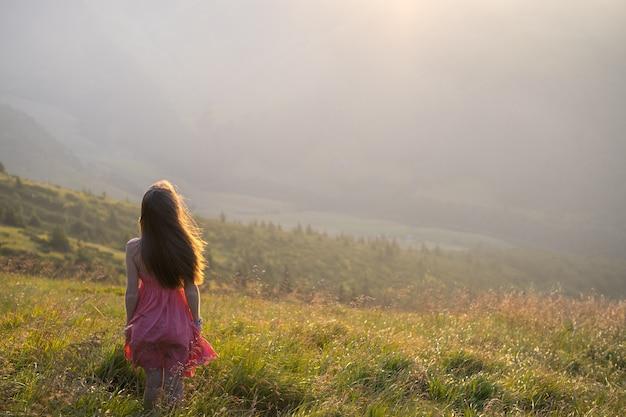 Jovem mulher vestida de vermelho andando num prado encosta em uma noite ventosa nas montanhas de verão.