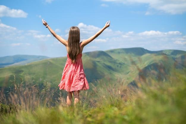 Jovem mulher vestida de vermelho de pé num prado gramado em um dia ventoso nas montanhas de verão, levantando as mãos, apreciando a vista da natureza.