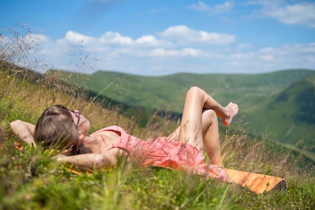 Jovem mulher vestida de vermelho deitada em um campo gramado verde, descansando em um dia ensolarado nas montanhas de verão, apreciando a vista da natureza.