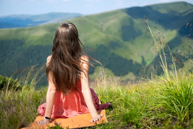 Jovem mulher vestida de vermelho, descansando em campo gramado verde, em um dia ensolarado nas montanhas de verão, apreciando a vista da natureza.