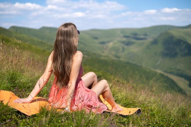 Jovem mulher vestida de vermelho, descansando em campo gramado verde, em um dia quente de sol nas montanhas de verão, apreciando a vista da natureza.