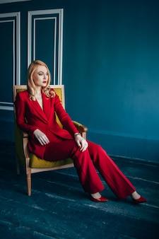 Jovem mulher vestida de vermelho está sentado em uma armadura amarela com paredes azuis bordadas azuis