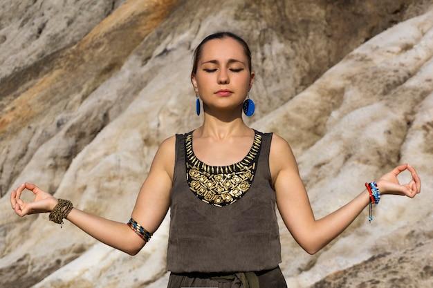 Jovem mulher vestida em estilo folclórico medita ao ar livre, segurando as mãos na posição gyan mudra