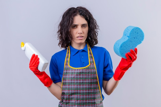 Jovem mulher vestindo avental e luvas de borracha, segurando a esponja e produtos de limpeza com expressão suspeita sobre parede branca