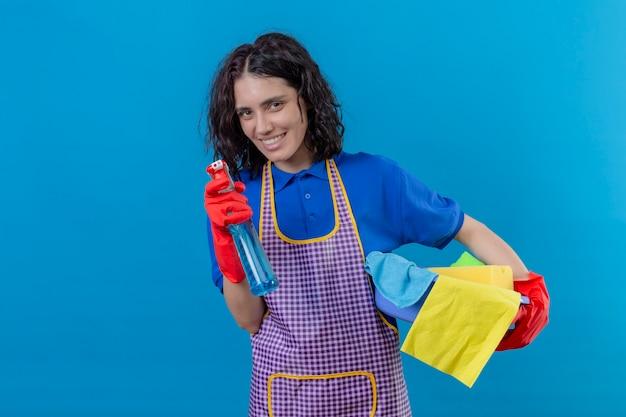 Jovem mulher vestindo avental e luvas de borracha segurando basing com ferramentas de limpeza e spray de limpeza sorrindo alegremente sobre parede azul