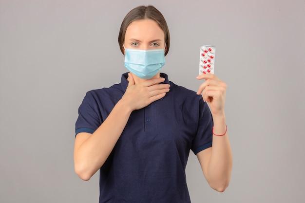 Jovem mulher vestindo camisa polo azul em máscara médica protetora segurando comprimidos de bolha na mão tocando seu pescoço em pé sobre fundo cinzento claro