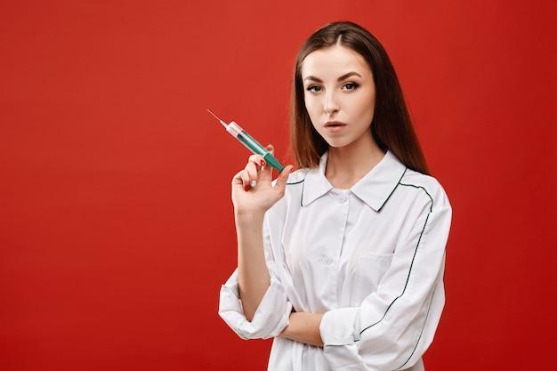 Jovem mulher vestindo jaleco branco com uma seringa nas mãos. os jovens enfermeiros prepararam uma seringa para vacinação. conceito de cuidados de saúde e medicina Foto Premium