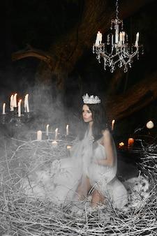 Jovem mulher vestindo lingerie de cetim, posando em um enorme ninho com velas no fundo