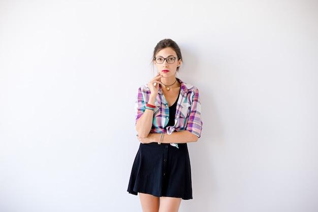 Jovem mulher vestindo óculos elegantes e camisa xadrez colorida
