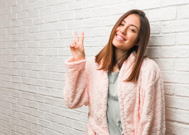 Jovem mulher vestindo pijama, fazendo um gesto de vitória
