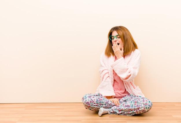 Jovem mulher vestindo pijama sentado em casa bocejando preguiçosamente de manhã cedo acordando e parecendo sonolento, cansado e entediado