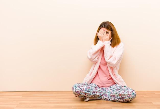 Jovem mulher vestindo pijama, sentado em casa cobrindo o rosto com as mãos, espreitando entre os dedos com expressão de surpresa e olhando para o lado