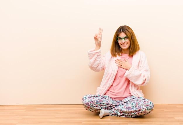Jovem mulher vestindo pijama, sentado em casa, olhando feliz, confiante e confiável, sorrindo e mostrando sinal de vitória, com uma atitude positiva