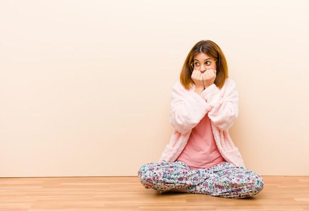 Jovem mulher vestindo pijama, sentado em casa olhando preocupado, ansioso, estressado e com medo, roer unhas e olhando para o espaço lateral da cópia