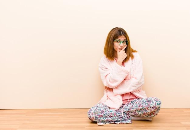 Jovem mulher vestindo pijama, sentado em casa, olhando sério, pensativo e desconfiado, com um braço cruzado e mão no queixo, opções de ponderação