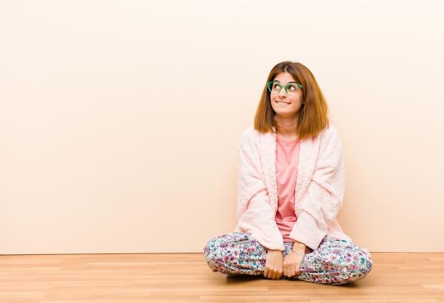 Jovem mulher vestindo pijama, sentado em casa pensando, pensando felizes pensamentos e idéias, sonhando acordado, olhando para copiar o espaço do lado
