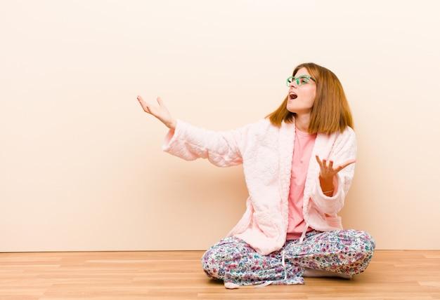 Jovem mulher vestindo pijama, sentado em casa realizando ópera ou cantando em um concerto ou show, sentindo-se romântico, artístico e apaixonado