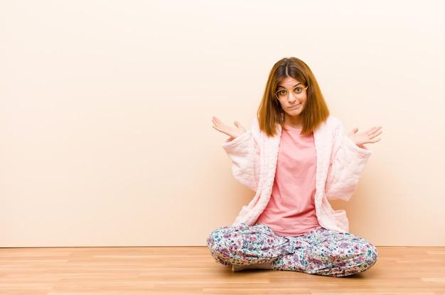 Jovem mulher vestindo pijama sentado em casa sentindo-se confuso e confuso, duvidando, ponderando ou escolhendo opções diferentes com expressão engraçada