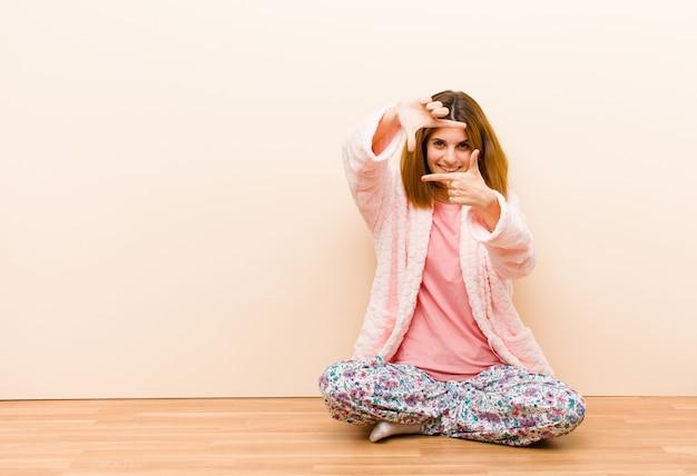 Jovem mulher vestindo pijama, sentado em casa, sentindo-se feliz, amigável e positivo, sorrindo e fazendo um retrato ou moldura com as mãos