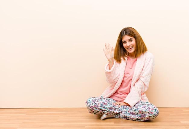 Jovem mulher vestindo pijama, sentado em casa, sorrindo alegremente e alegremente, acenando com a mão, dando as boas-vindas e cumprimentando-o ou dizendo adeus