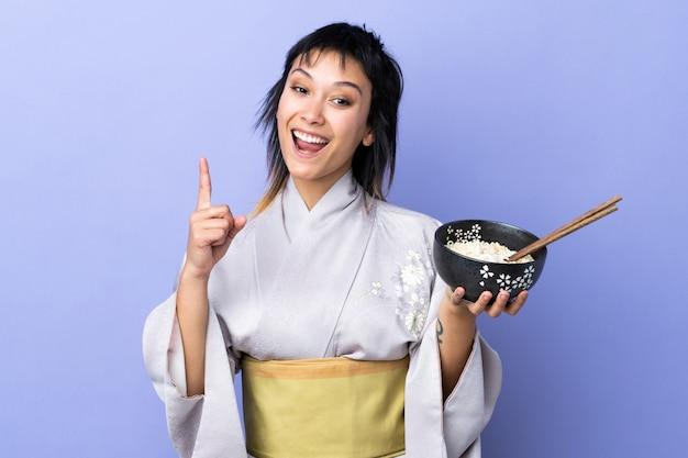 Jovem mulher vestindo quimono azul isolado apontando uma ótima idéia, mantendo uma tigela de macarrão com pauzinhos
