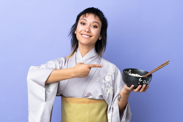 Jovem mulher vestindo quimono azul isolado e apontando-o, mantendo uma tigela de macarrão com pauzinhos