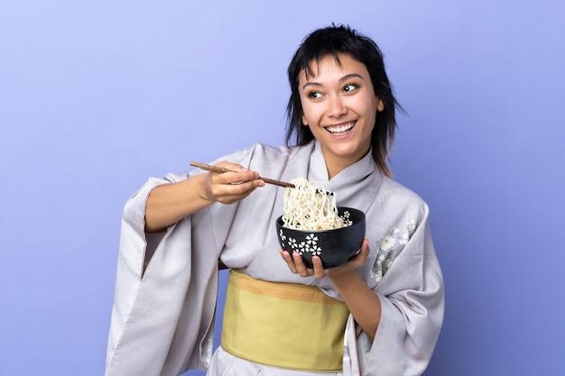 Jovem mulher vestindo quimono azul isolado, segurando uma tigela de macarrão com pauzinhos e olhando para cima