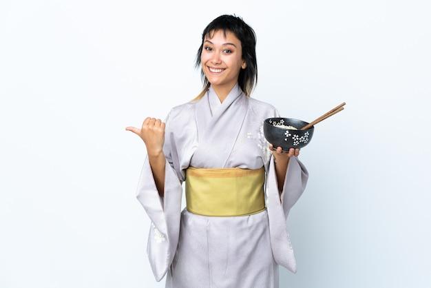Jovem mulher vestindo quimono segurando uma tigela de macarrão sobre parede branca isolada, apontando para o lado para apresentar um produto
