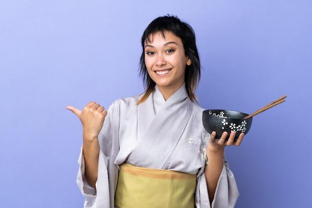 Jovem mulher vestindo quimono sobre azul isolado apontando para o lado para apresentar um produto, mantendo uma tigela de macarrão com pauzinhos