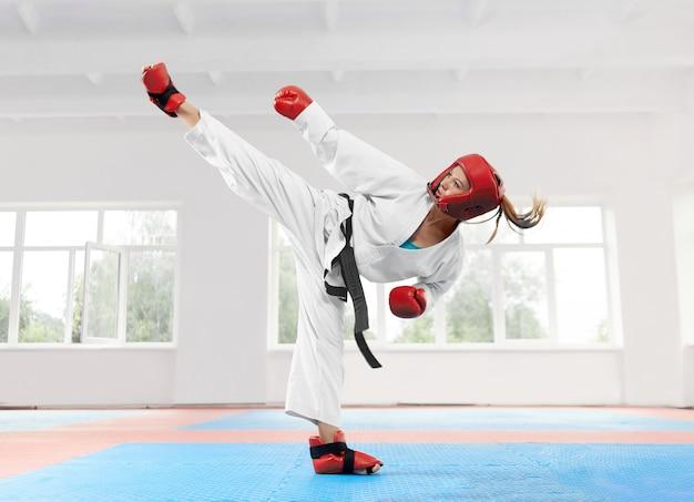 Jovem mulher vestindo quimono tradicional praticando seu karatê em movimento.