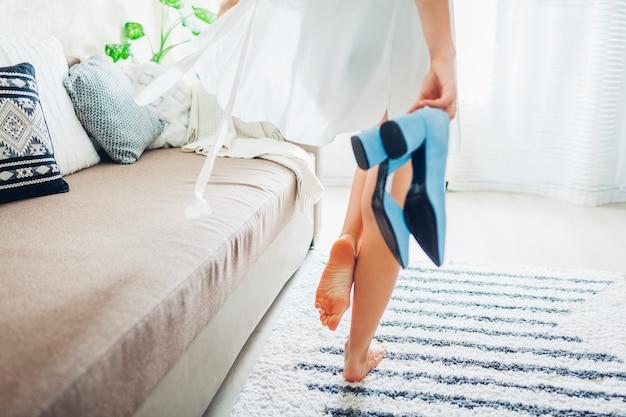 Jovem mulher vestindo roupão de seda e segurando sapatos azuis em casa, noiva no dia do casamento