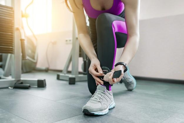 Jovem mulher vestindo tiras de tornozelo de couro se prepara para exercitar na máquina de fitness
