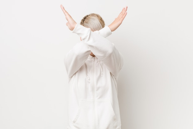 Jovem mulher vestindo um capuz branco, mantendo os dois braços cruzados