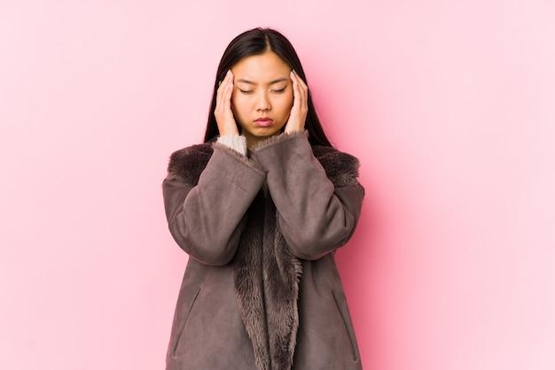 Jovem mulher vestindo um casaco tocando os templos e tendo dor de cabeça.