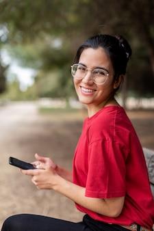 Jovem mulher vestindo uma camisa vermelha e óculos está usando o telefone em um parque enquanto sorrindo para a câmera.