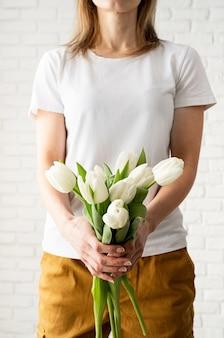 Jovem mulher vestindo uma camiseta branca em branco segurando flores de tulipas.