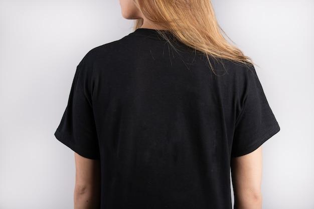 Jovem mulher vestindo uma camiseta preta de manga curta com uma parede branca ao fundo