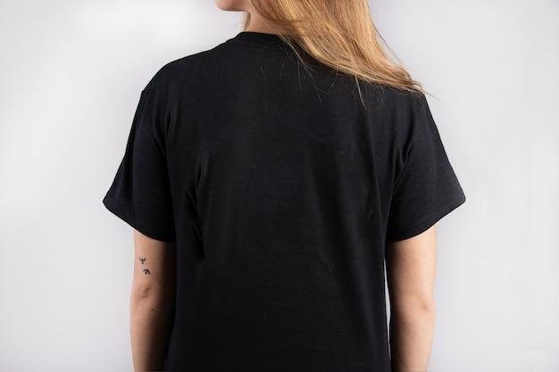 Jovem mulher vestindo uma camiseta preta de manga curta com uma parede branca