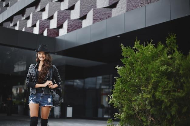 Jovem mulher vestindo uma jaqueta de couro de chapéu e shorts jeans, sorrindo em menina modelo de fundo urbano em.